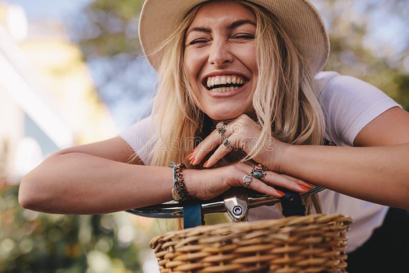 Donna attraente che ride all'aperto con la sua bici immagine stock