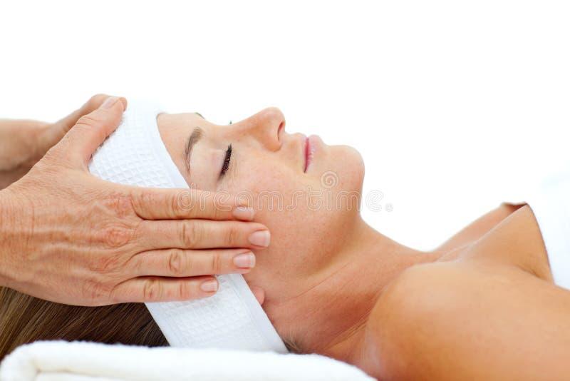 Donna attraente che si distende con il massaggio capo immagine stock