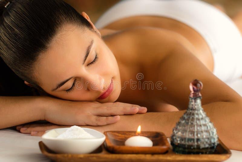 Donna attraente che si rilassa nella stazione termale accanto alla candela ed all'olio essenziale immagine stock