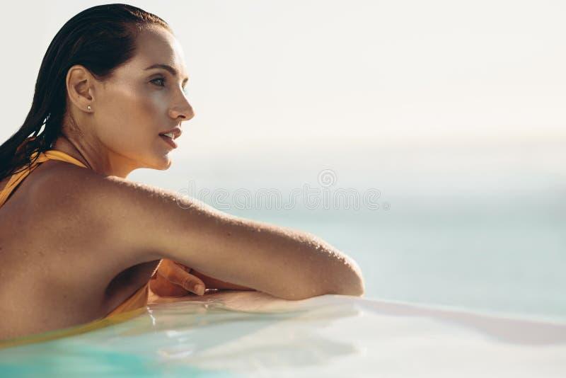Donna attraente che si rilassa nello stagno di infinito fotografia stock libera da diritti