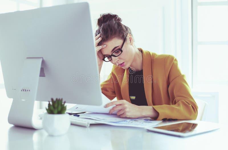 Donna attraente che si siede allo scrittorio in ufficio, lavorando con il computer portatile, tenente documento immagine stock