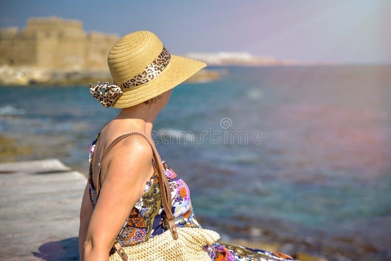 Donna attraente che si siede sul pilastro immagine stock