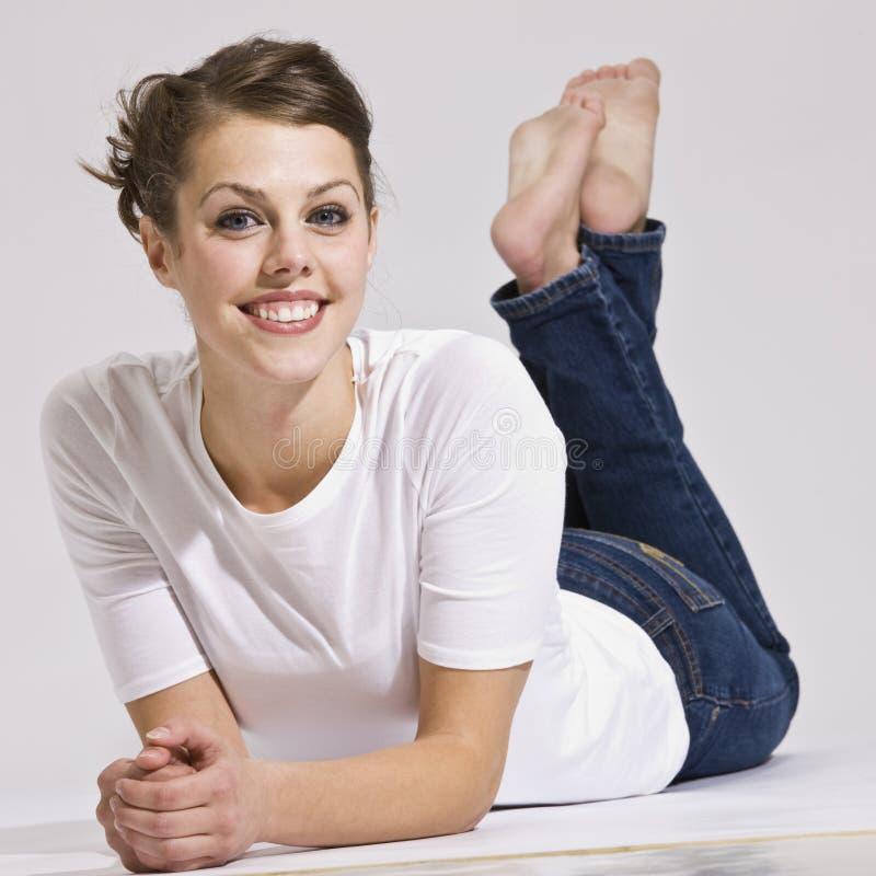 Donna attraente che si trova giù e che sorride fotografia stock libera da diritti