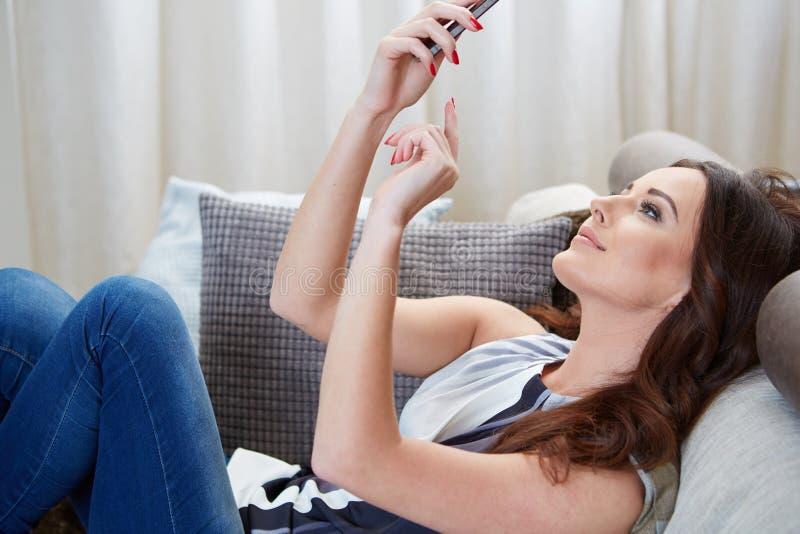 Donna attraente che sorride come legge gli sms fotografia stock libera da diritti