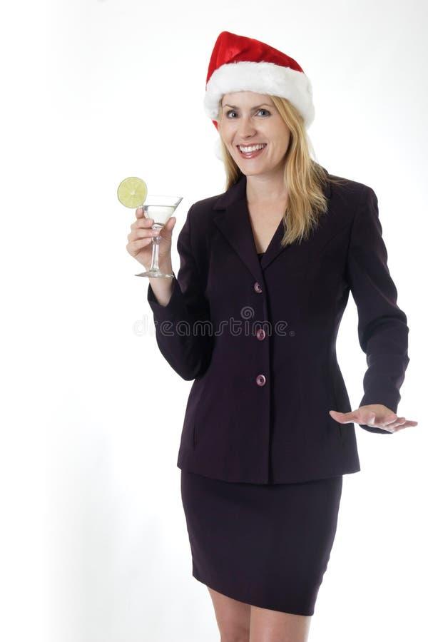 Donna attraente che tiene un martini alla festa di Natale dell'ufficio fotografia stock