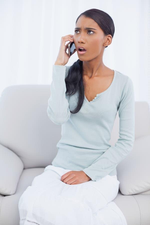 Donna attraente colpita che si siede sul sofà accogliente che ha un telefono caloria fotografie stock