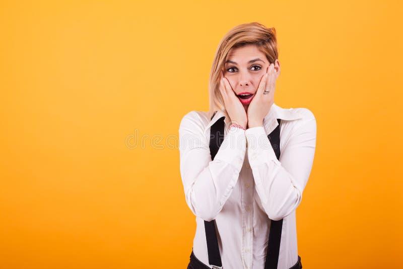 Donna attraente colpita e che tiene le mani sulle sue guance sopra fondo giallo immagine stock