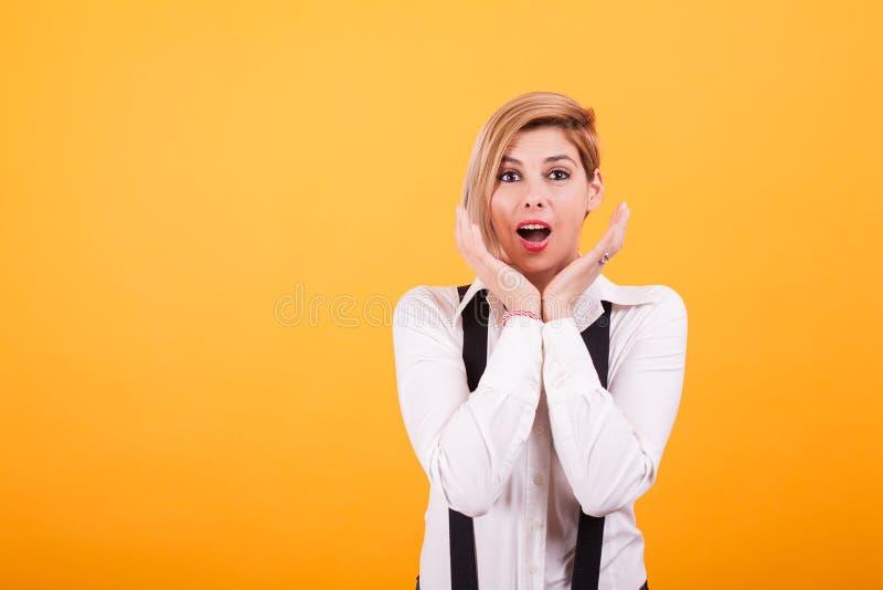 Donna attraente con capelli biondi che esaminano colpiti la macchina fotografica sopra fondo giallo fotografia stock