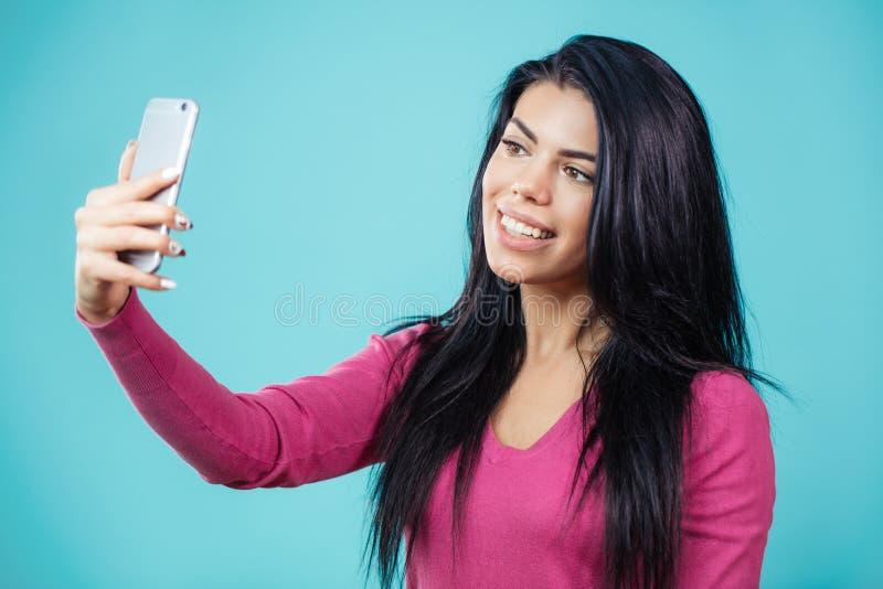Donna attraente con capelli neri facendo uso del suo smartphone per selfie immagini stock libere da diritti