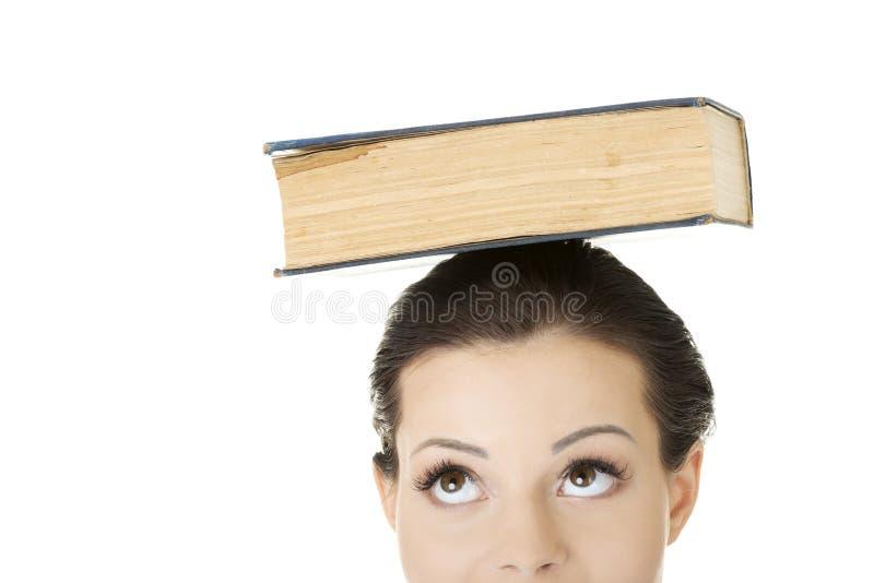 Donna attraente con il libro sulla testa fotografie stock libere da diritti
