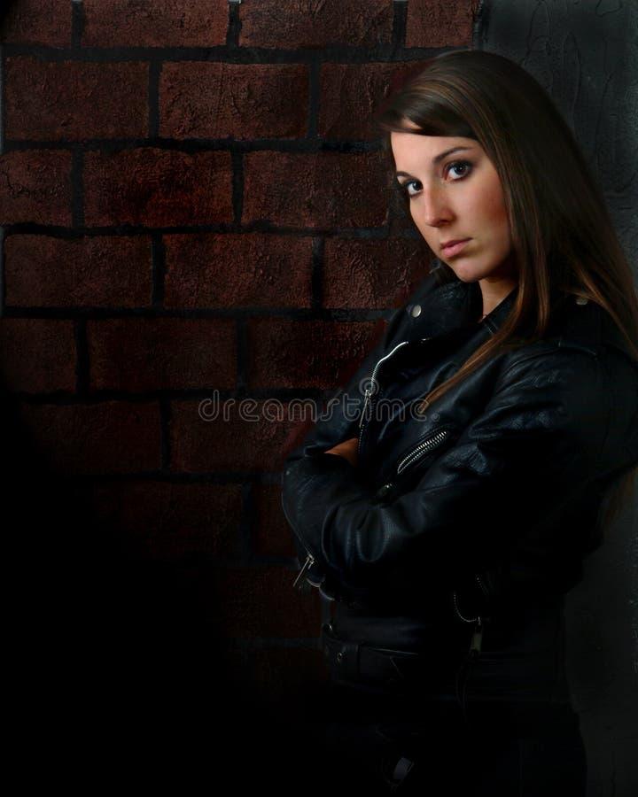 Donna attraente con l'atteggiamento ed il muro di mattoni immagini stock libere da diritti