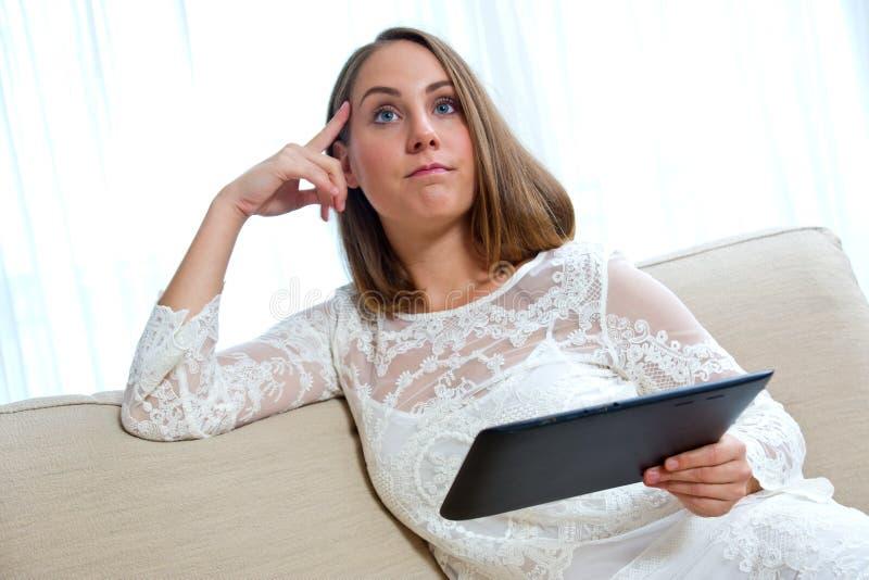 Donna attraente con la compressa a casa immagine stock libera da diritti