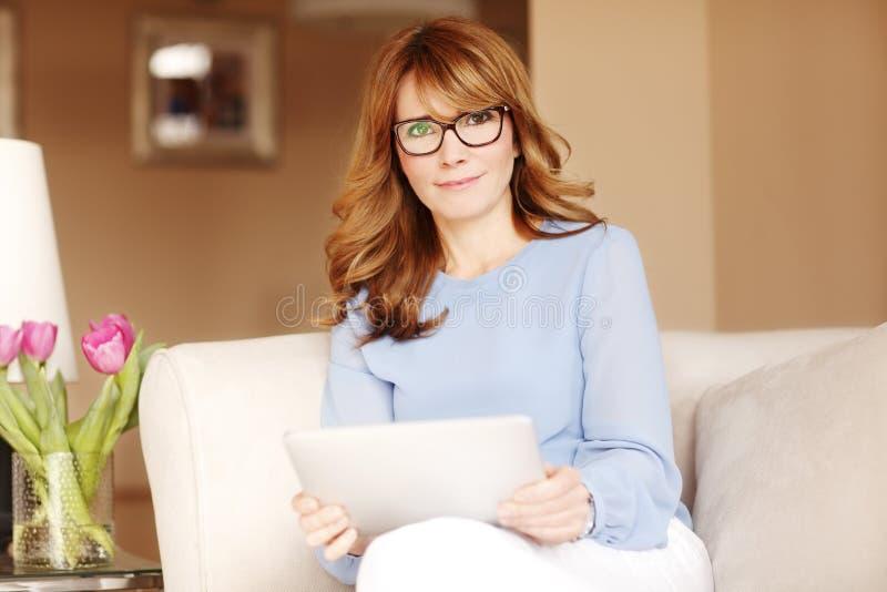 Donna attraente con la compressa digitale immagine stock