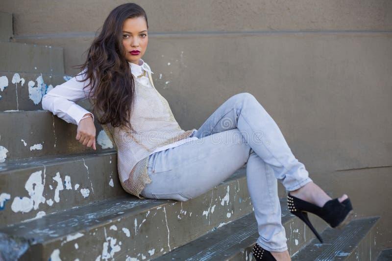 Donna attraente con le labbra rosse che si siedono sulla posa delle scale immagine stock