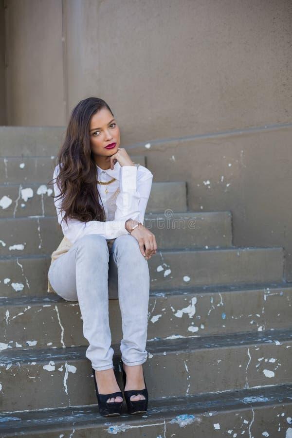 Donna attraente con le labbra rosse che si siedono sulle scale immagine stock libera da diritti