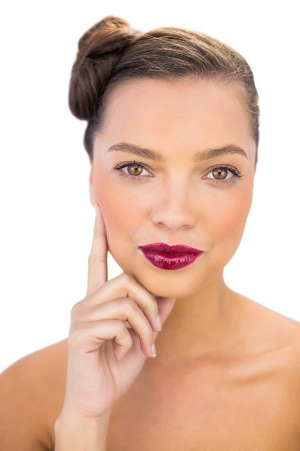 Donna attraente con le labbra rosse che toccano la sua guancia fotografie stock libere da diritti