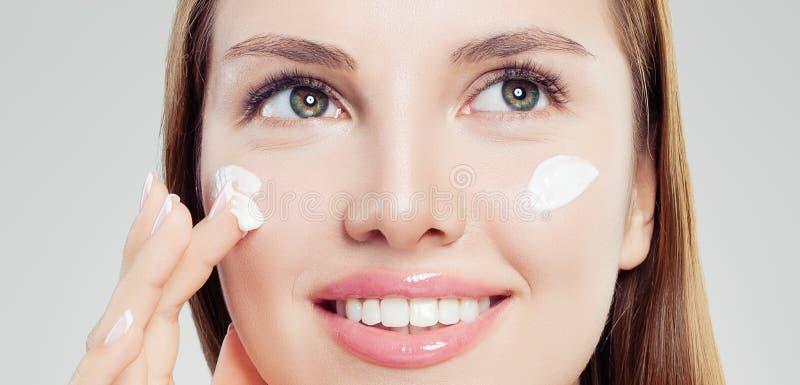Donna attraente con pelle sana che applica crema cosmetica, primo piano del fronte Skincare, bellezza e concetto facciale di trat fotografia stock libera da diritti