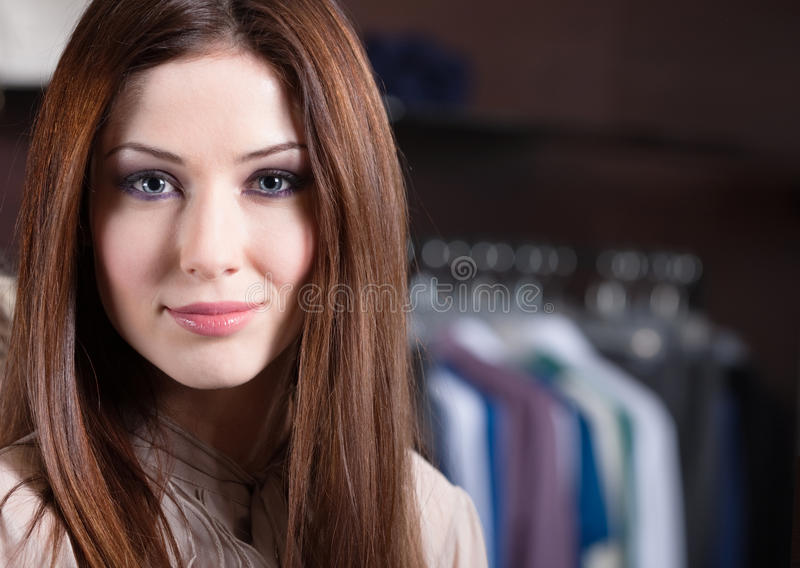 Donna attraente contro lo sfondo dei vestiti immagini stock