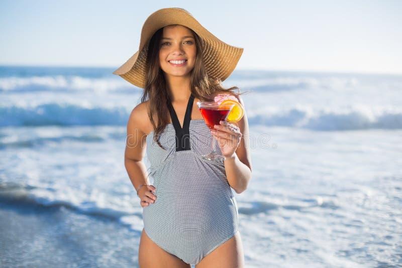 Donna attraente in costume da bagno con il cocktail della tenuta del cappello di paglia fotografia stock libera da diritti