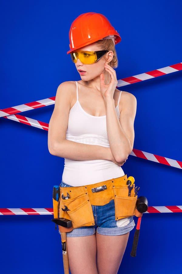 Donna attraente del costruttore in camicia bianca, cinghia del costruttore, casco, b fotografia stock libera da diritti