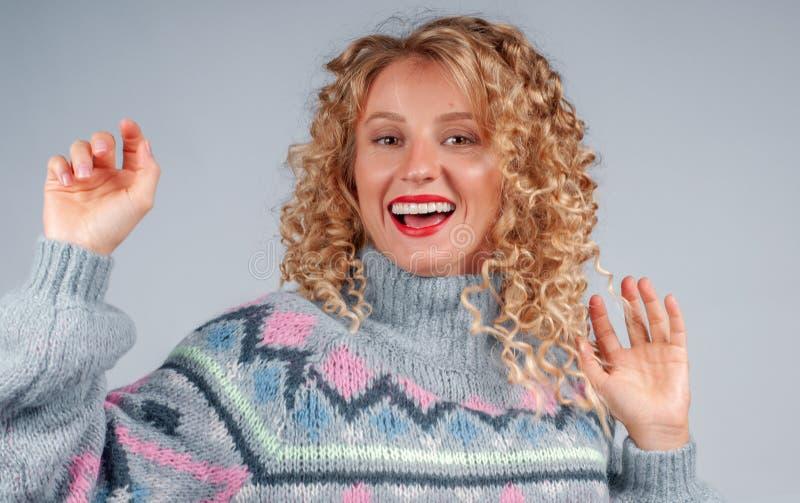 Donna attraente dello studente con capelli ricci vestiti in maglione caldo immagini stock libere da diritti
