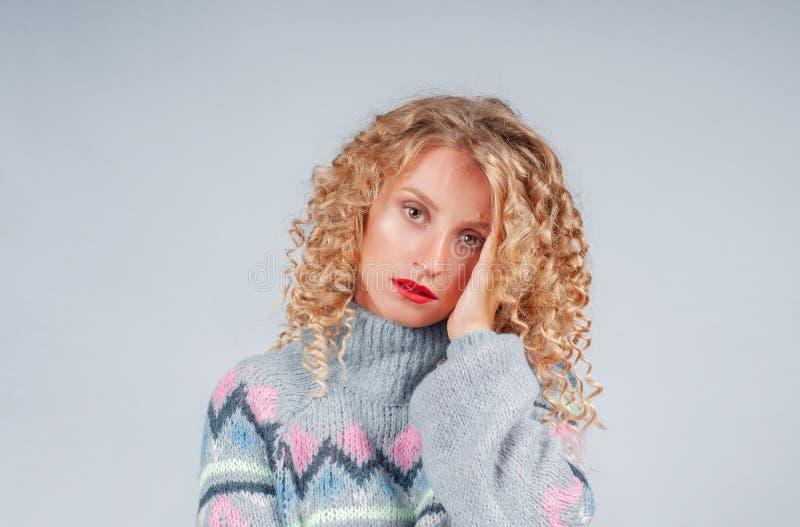 Donna attraente dello studente con capelli ricci vestiti in maglione caldo fotografia stock