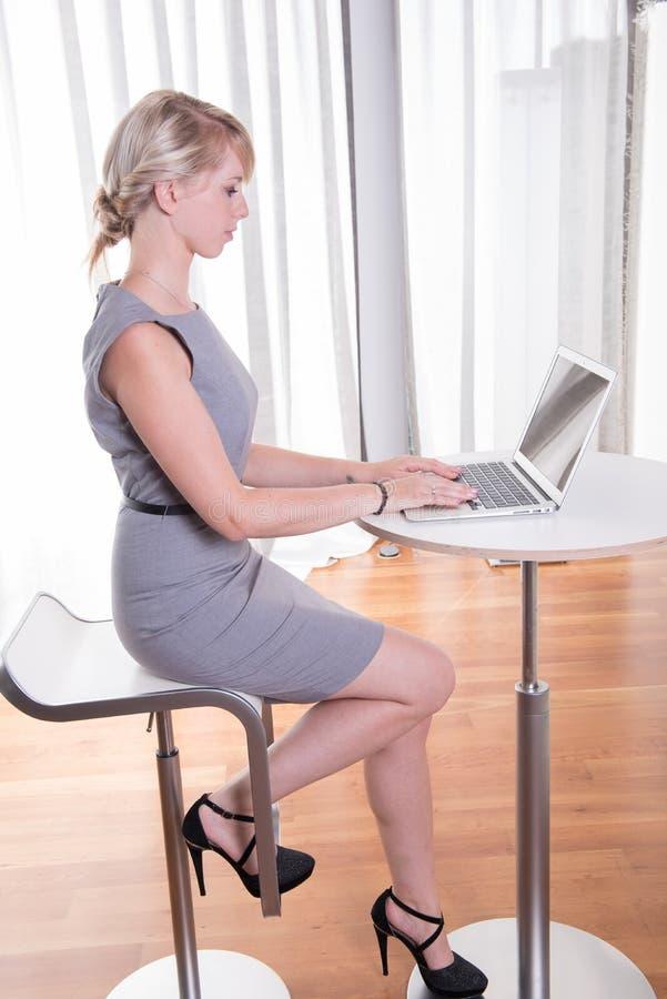 Donna attraente di affari del ritratto giovane con il computer portatile immagini stock libere da diritti