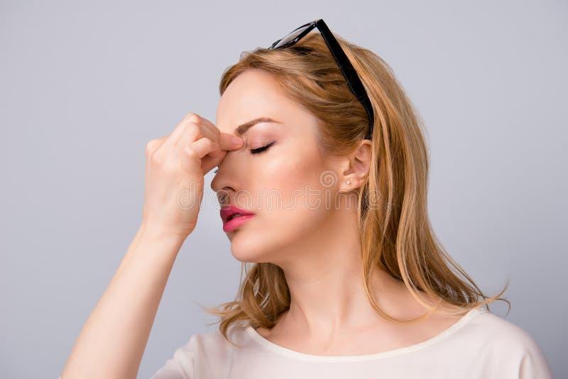 Donna attraente di affari stanca sul lavoro che soffre dall'emicrania isolata su fondo grigio che soffre dal naso touvhing di emi immagine stock