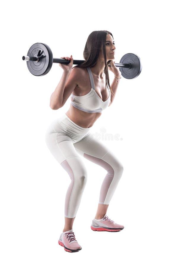 Donna attraente di forma fisica sicura motivata che fa gli esercizi tozzi della palestra con il bilanciere immagini stock libere da diritti
