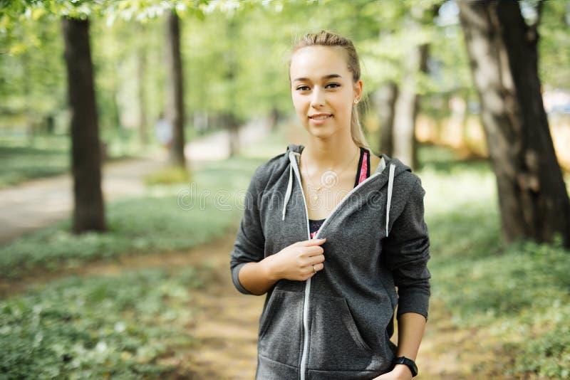 Donna attraente di misura in abiti sportivi che si prepara all'aperto Ritratto dell'atleta femminile con l'ente perfetto che ripo fotografia stock libera da diritti