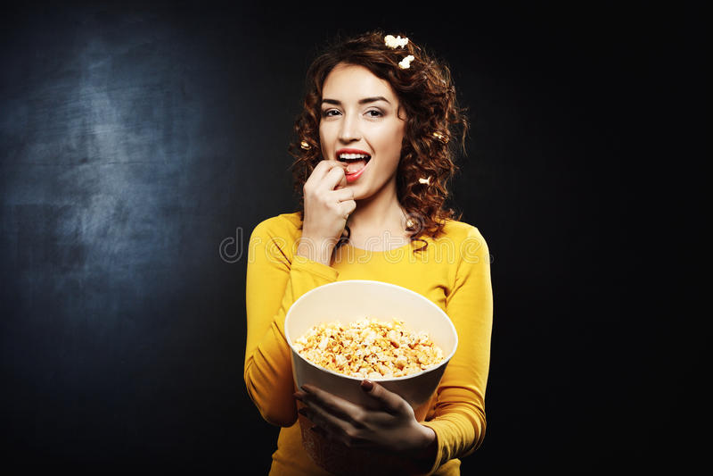 Donna attraente divertente che mangia popcorn dolce salato saporito al cinema fotografie stock libere da diritti