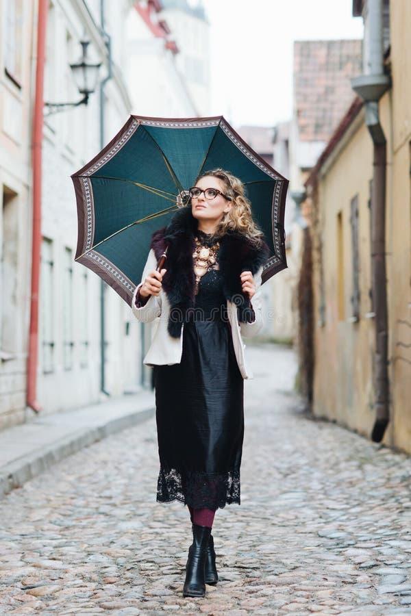 Donna attraente e alla moda che cammina con un ombrello fotografia stock