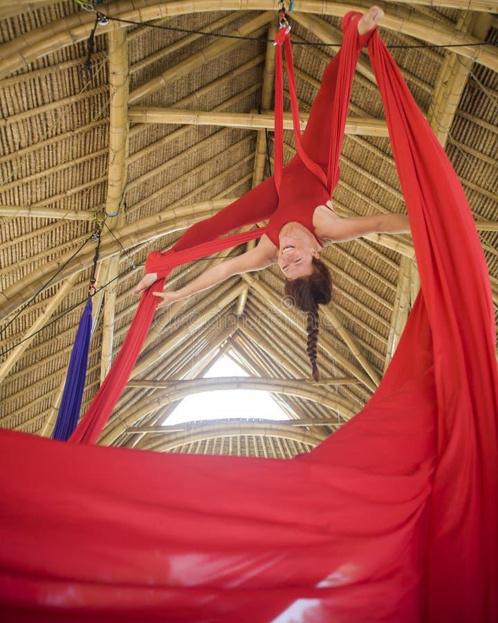 Donna attraente ed atletica del aerialist che pende dal tessuto di seta che fa addestramento ballante aereo di allenamento felice fotografie stock