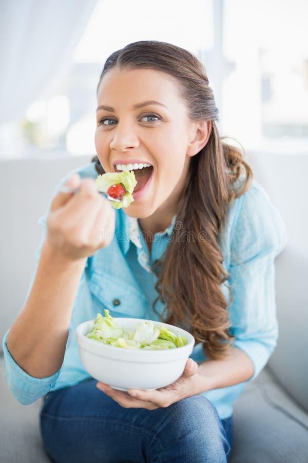 Donna attraente felice che mangia insalata sana fotografia stock
