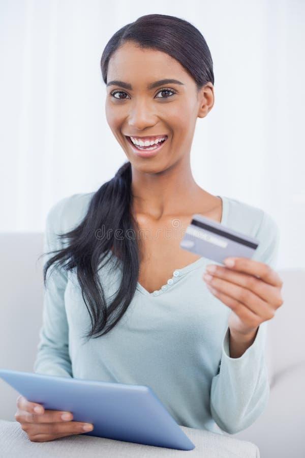 Donna attraente felice che per mezzo del suo pc della compressa per comprare online fotografia stock libera da diritti