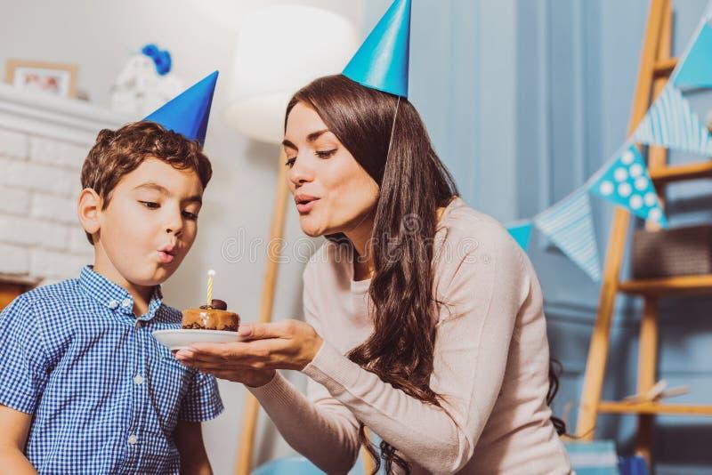 Donna attraente felice che propone torta di compleanno al ragazzo fotografia stock