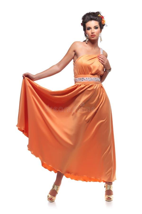 Donna attraente giovane che tira il suo vestito lungo fotografia stock