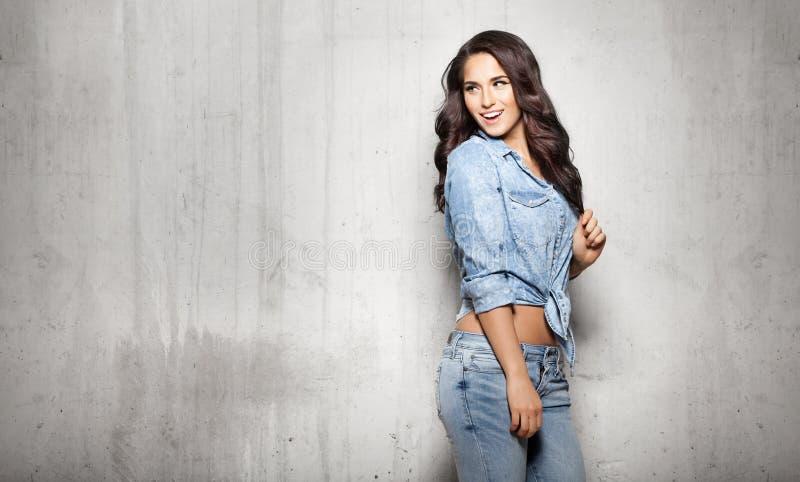 Donna attraente in jeans che toccano i suoi capelli immagine stock libera da diritti
