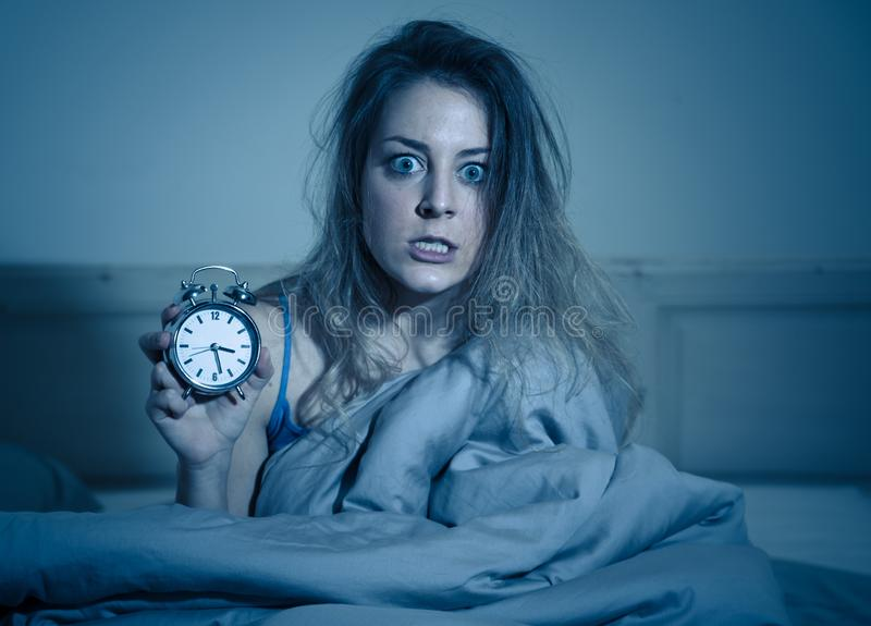 Donna attraente a letto che mostra sveglia alla sensibilità della macchina fotografica preoccupata, sollecitato e insonne immagine stock libera da diritti