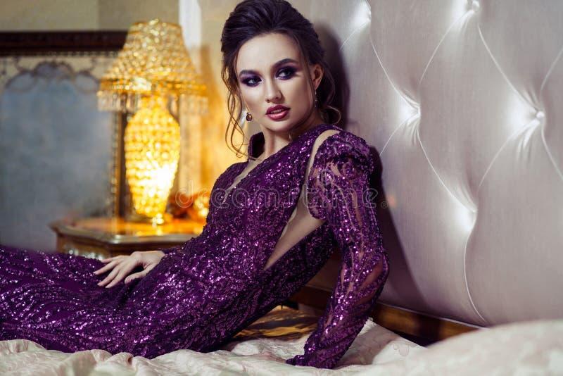 Donna attraente nell'uguagliare vestito brillante porpora, acconciatura e uff immagine stock libera da diritti