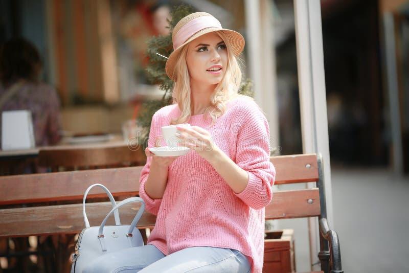 Donna attraente nell'umore romantico che sorride nella felicità che si siede alla tavola che porta rivestimento rosa immagine stock