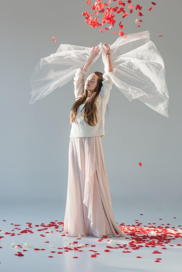 donna attraente nella condizione alla moda dell'attrezzatura di inverno con le mani sollevate sotto i petali di rose rosse di cad fotografia stock libera da diritti