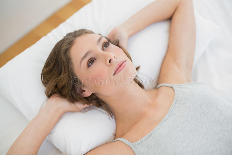 Donna attraente premurosa che si trova sul suo letto fotografia stock