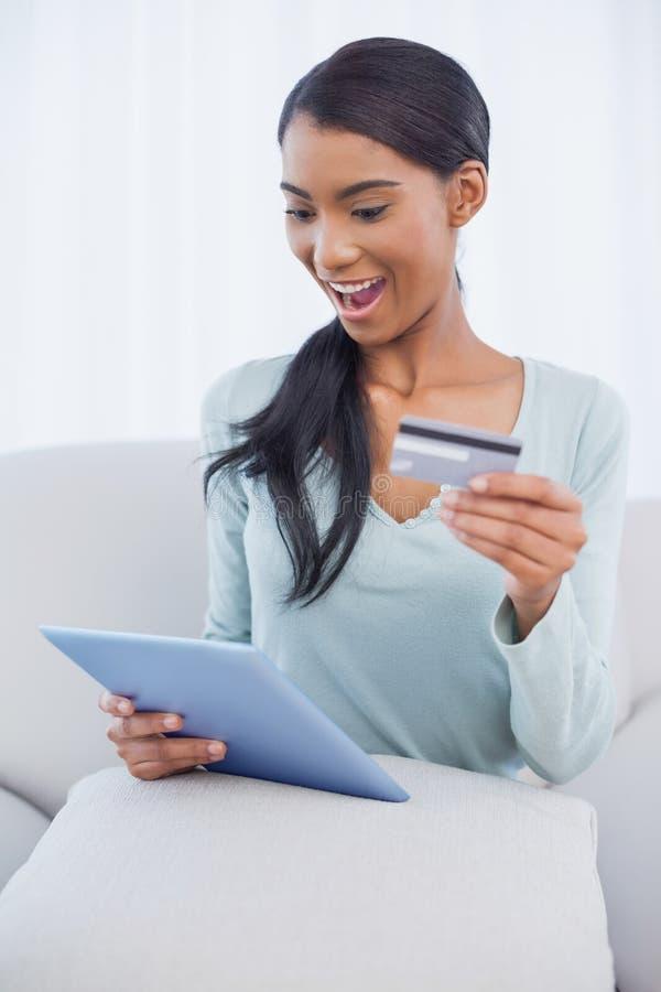 Donna attraente sorpresa che per mezzo del suo pc della compressa per comprare online fotografie stock libere da diritti