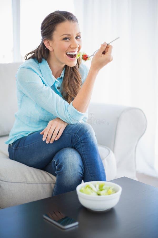 Donna attraente sorridente che mangia insalata sana immagine stock libera da diritti