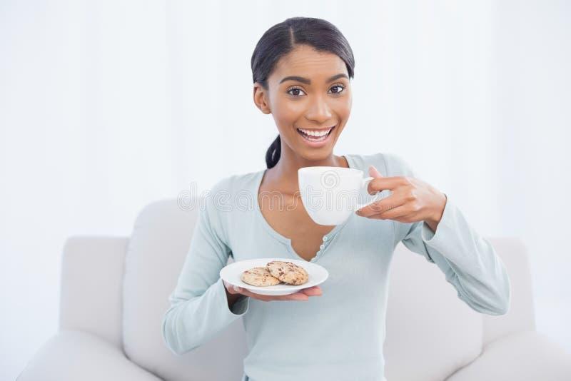 Donna attraente sorridente che si siede sul caffè accogliente della tenuta del sofà e immagini stock libere da diritti