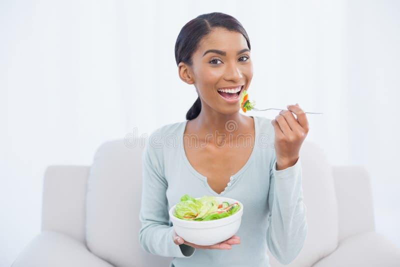 Donna attraente sorridente che si siede sul sofà accogliente che mangia insalata fotografia stock