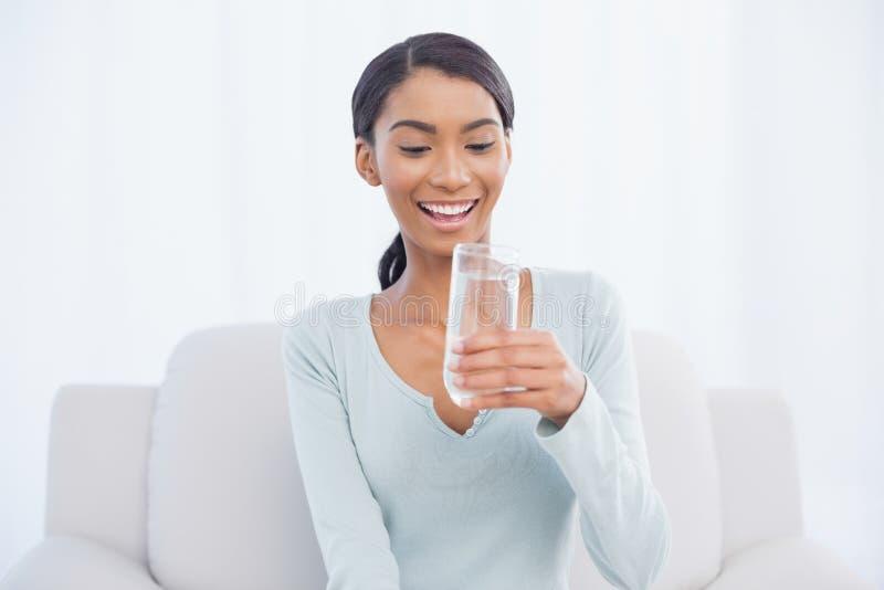 Donna attraente sorridente che si siede sull'acqua potabile del sofà accogliente fotografie stock libere da diritti