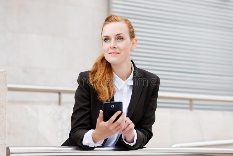 Donna attraente sorridente con Smartphone immagini stock libere da diritti