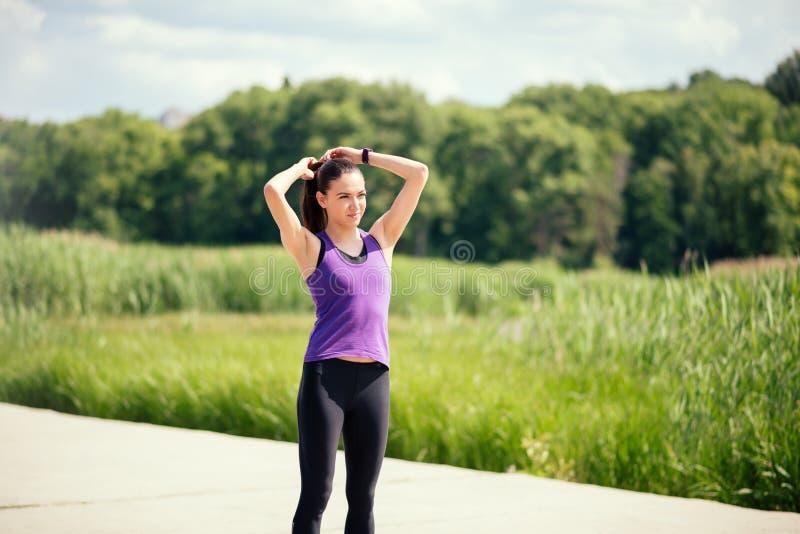 Donna attraente sportiva fare una coda e una ricreazione prima o dopo l'allenamento e un funzionamento di cavallino sul fondo del fotografia stock